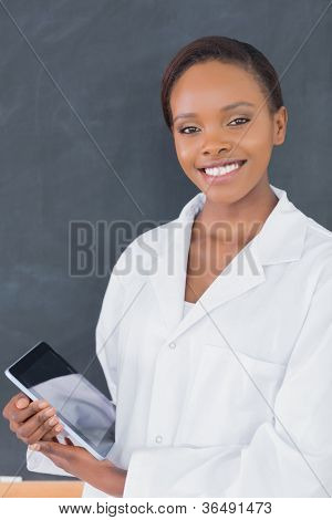 Teacher holding a tablet computer while looking at camera in a classroom