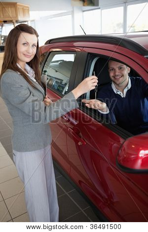 Man tending his hand while receiving car keys in a dealership