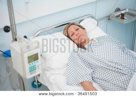 Female patient lying on a bed while looking at camera in hospital ward