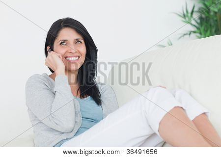 Woman smiling while telephoning in a living room
