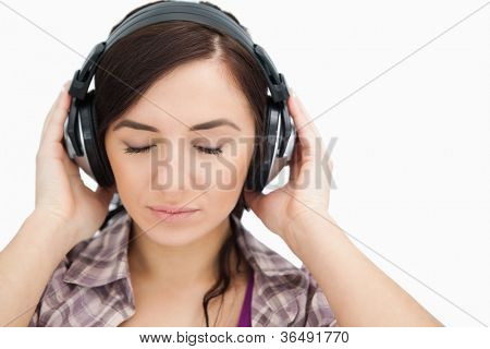 Brunette with headphones closing her eyes against white background
