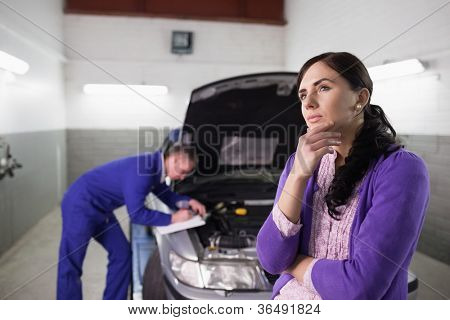 Thoughtful woman next to a car in a garage