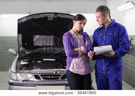 Mechanic showing the quotation to a client in a garage