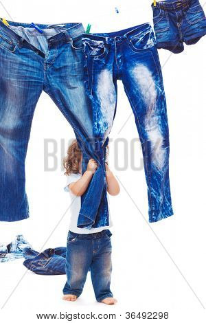 Curly toddler boy pulling jeans