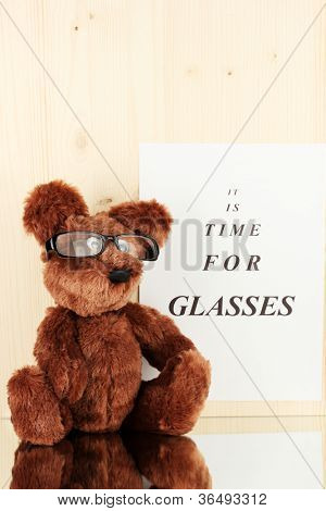 Eyesight test chart with glasses and with toy on wooden background close-up