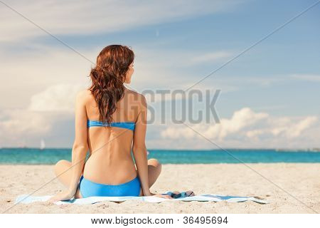 picture of woman practicing yoga lotus pose on the beach.