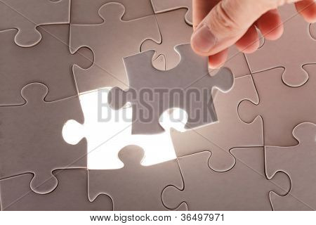 hand holding puzzle piece