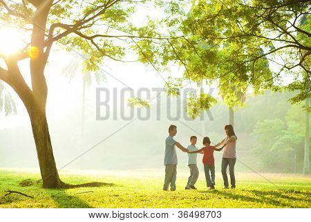 Happy Asian family holding hands in a circle and running over green lawn