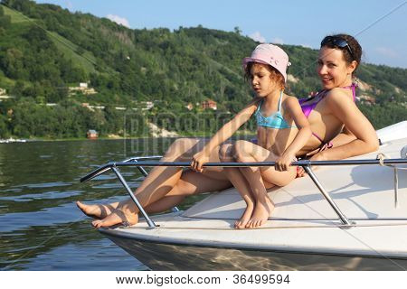 Mother daughter sunbathing on cutter on river, focus on daughter
