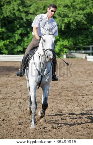 Jockey in glasses riding horse on hippodrome