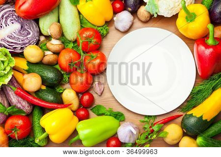 Fresh Organic Vegetables on wooden Table Around White Plate / with copy space for your text