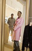 stock photo of overcoats  - Happy African American woman trying overcoat with man looking at her in store - JPG