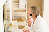 Senior woman apply make-up powder in front of bathroom mirror