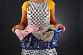Closeup of a homemaker in an apron holding a basket full of laundry. Horizontal format over a light