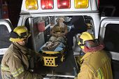 image of firemen  - Two fireman looking at an injured person in an ambulance - JPG