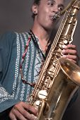 image of musical instruments  - Portrait of young trendy man playing saxophone  - JPG