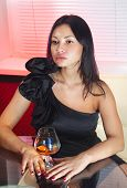 stock photo of bounce house  - beautiful woman in black dress on sofa with glass of brandy - JPG