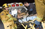 picture of stretcher  - Emergency service professionals carrying patient on stretcher in ambulance - JPG