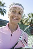 Portrait of a happy senior woman holding tennis racquet