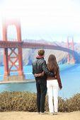 San Francisco Golden Gate Bridge. Young traveling couple enjoying view of the travel icon landmark and San Francisco Bay. poster