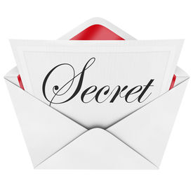 stock photo of cursive  - An envelope revealing a note with the handwritten cursive word Secret - JPG