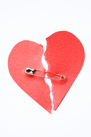 picture of broken heart  - Red paper heart torn in half secured with safety pin on white background