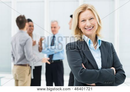 Portrait Of Happy Senior Businesswoman In Office With Her Colleagues