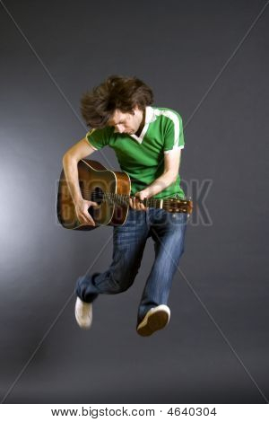 Passionate Guitarist Jumps Isolated On Black Background