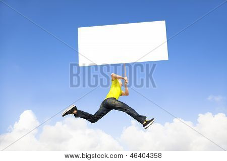 Young Man Holding Blank Board Jumping Against Blue Sky