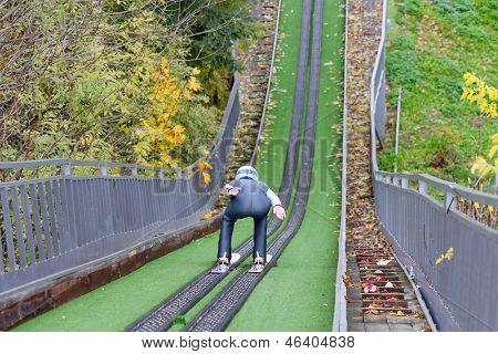 Back of man descending from artificial hill on skis in helmet at autumn outdoors.
