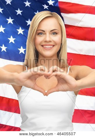 woman in white tank showing heart shape with hands over american flag