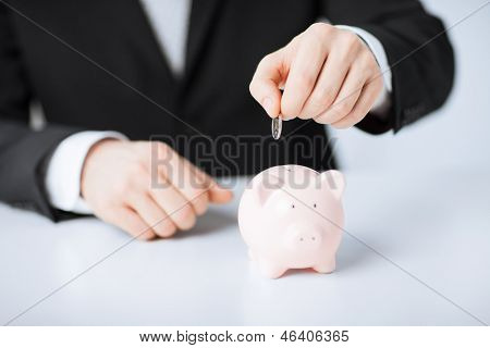 picture of man putting coin into small piggy bank