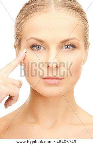face of beautiful woman pointing at her eye area