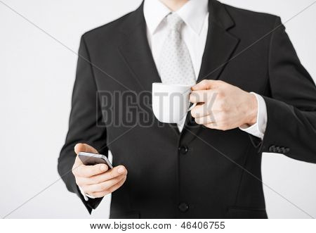 close up of man with smartphone and cup of coffee