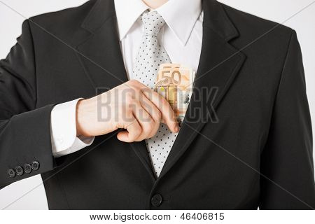 man hand putting euro cash money into suit pocket