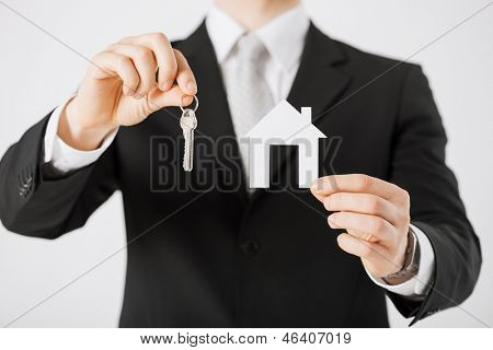 man hand holding house keys and paper house