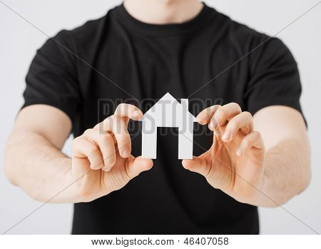 picture of man hands holding paper house