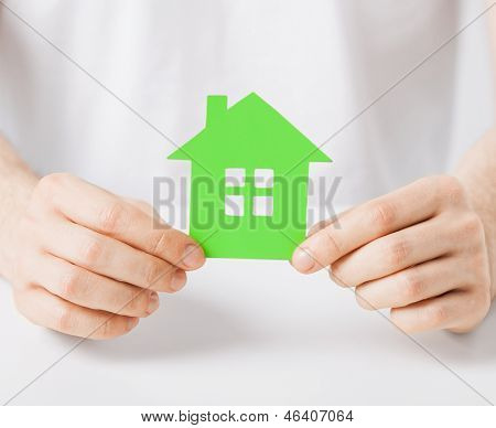 closeup picture of man hands holding green house