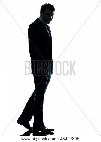 one caucasian business man sad full length   in silhouette studio isolated on white background