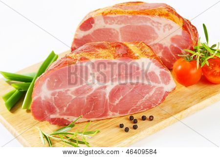 two block of pork ham with tomatoes and onion a cutting board