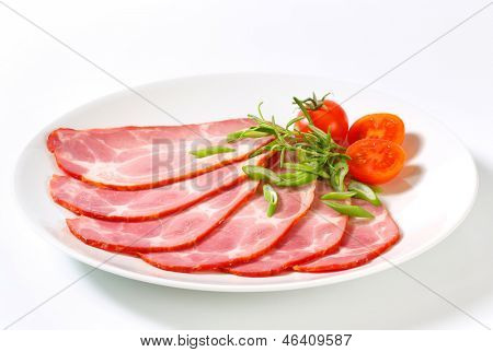 sliced pork neck with cherry tomatoes and spring onion on a round plate