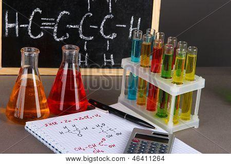 Tubos de ensaio com líquidos coloridos e fórmulas em fundo cinza