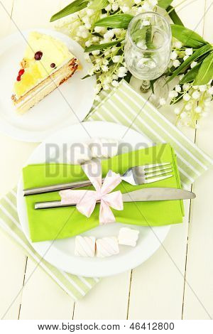 Table setting in white and green tones on color  wooden background