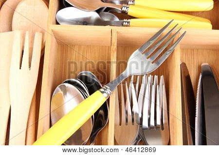 Checked cutlery in wooden cutlery box close up