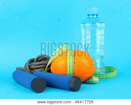 Orange with measuring tape,skipping rope and bottle of water, on color background