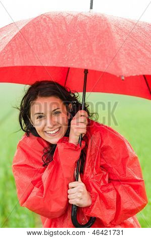 Wet young girl in raincoat enjoying rainfall with umbrella