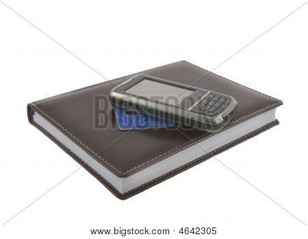 Closeup Of Brown Notebook.credit Kard And Mobile Phone On It Isolated Over White