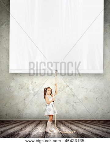 Little pretty girl pulling blank banner. Place for text