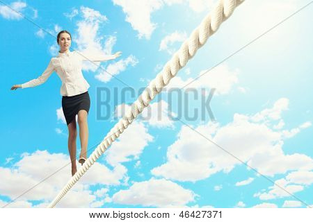 Image of businesswoman balancing on rope. Risk concept