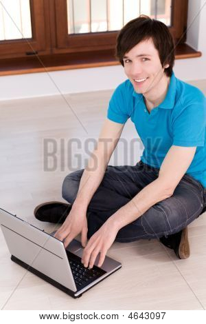 Young Man Sitting On Floor Using Laptop